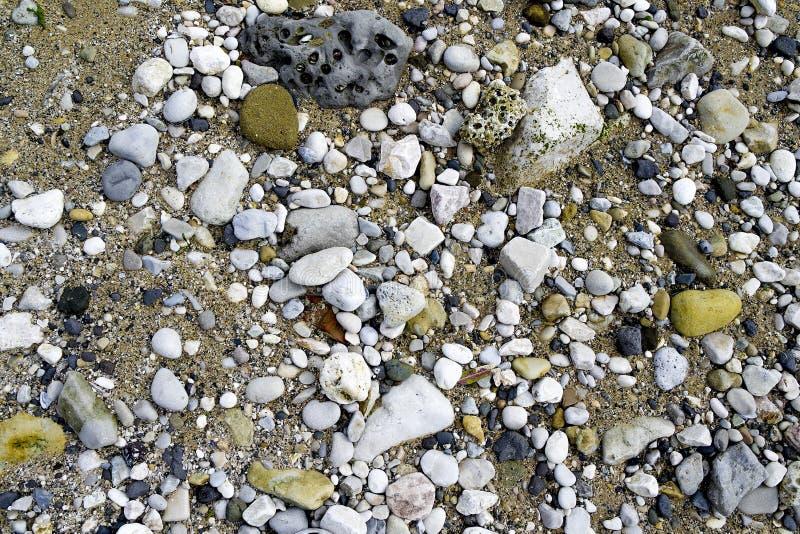 Pietre nere grige bianche sulla sabbia immagine stock