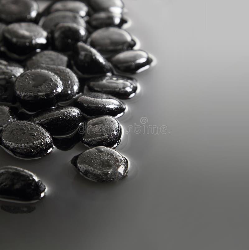Pietre nere sul fondo dell'acqua fotografia stock libera da diritti