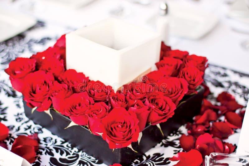 Pieza central con las flores y la vela rojas imagen de archivo libre de regalías