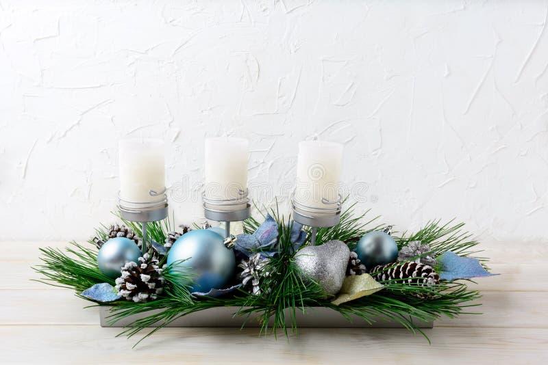 Pieza central de la tabla de la Navidad con tres velas y el ornamento azul fotos de archivo