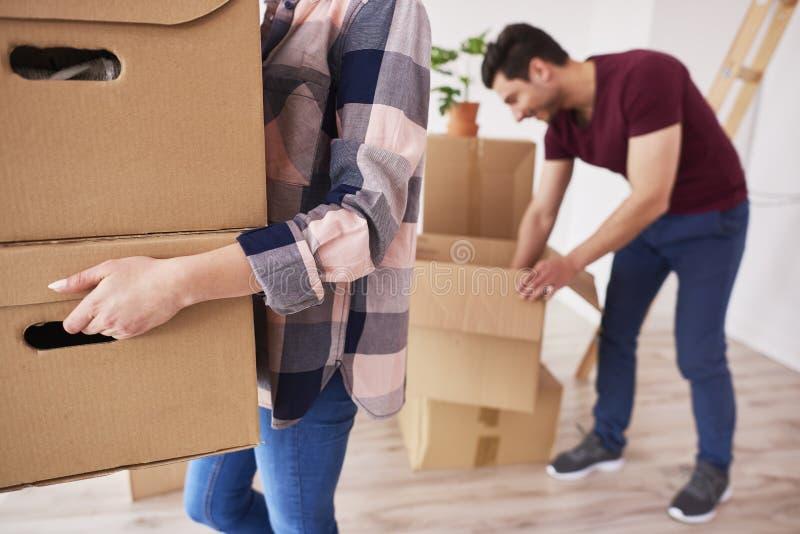 Pieza de cajas de cartón de la mujer que llevan en el nuevo apartamento imagen de archivo