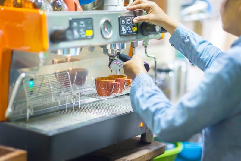 Pieza de la vista lateral de barista que hace el café mientras que se coloca en la cafetería imagen de archivo libre de regalías