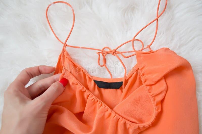 Pieza de una blusa anaranjada en una mano femenina, piel blanca en un fondo concepto de moda imágenes de archivo libres de regalías