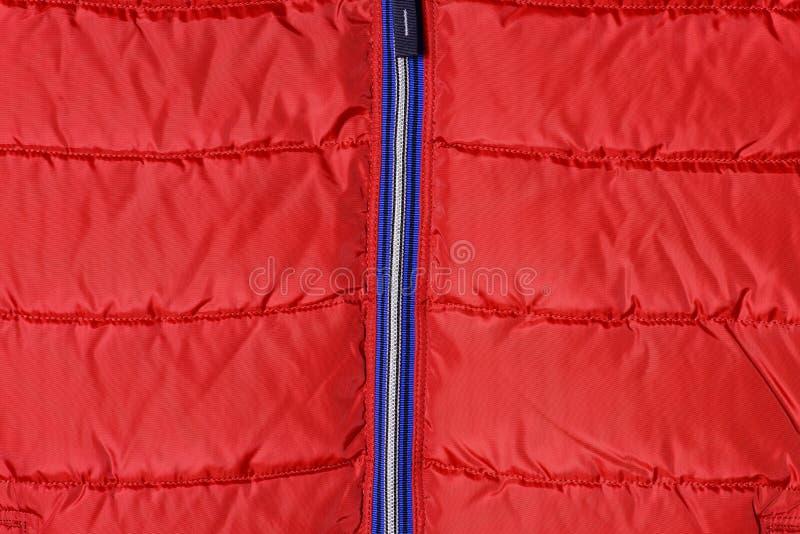 Pieza de una chaqueta del ` s de los hombres rojos abajo con una cremallera azul fotos de archivo