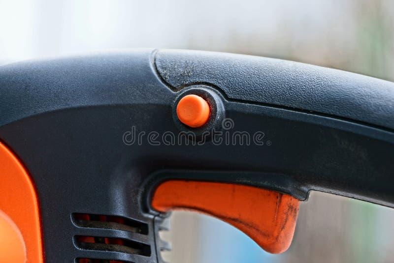 Pieza de una herramienta eléctrica con un botón anaranjado y un disparador en una manija plástica negra imagenes de archivo