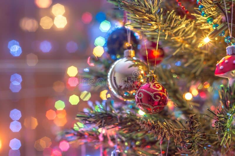 Pieza del árbol de navidad, con las bolas de cristal coloridas, las pequeñas decoraciones y los reflejos de luz coloridos fotografía de archivo libre de regalías