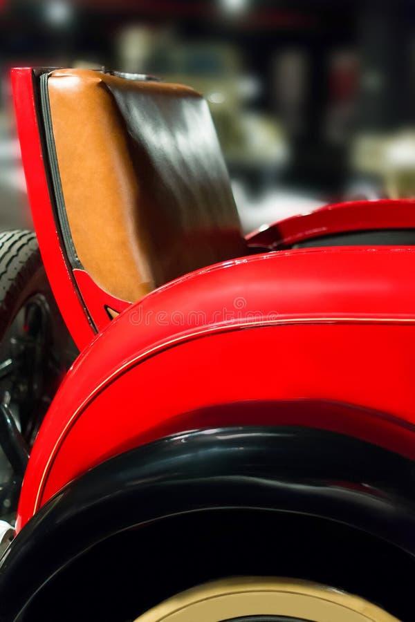 Pieza del asiento y del parachoques trasero de cuero con la rueda del coche del vintage fotografía de archivo libre de regalías