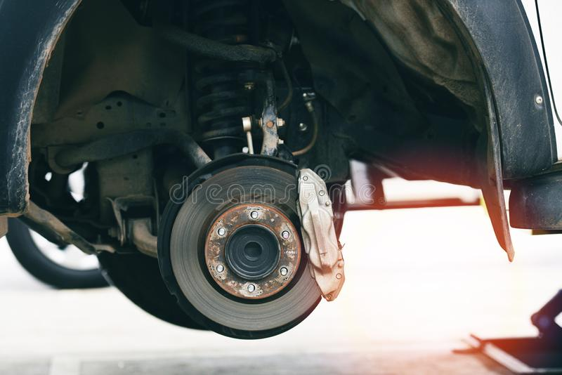 Pieza del coche de los frenos de disco en el garaje - el disco del freno del coche de la recogida aumentó en la elevación para ca imagenes de archivo