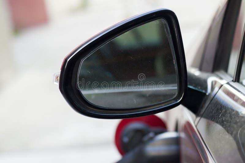 Pieza del detalle del primer del espejo de coche trasero sucio de la vista lateral con la reflexión borrosa en el fondo blanco de imagenes de archivo