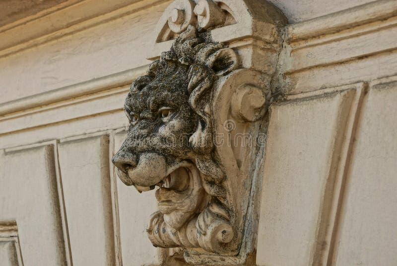Pieza del muro de cemento marrón viejo de la cerca con una escultura de la cabeza de un león imágenes de archivo libres de regalías