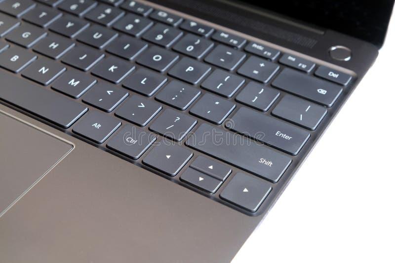 Pieza del teclado del ordenador portátil y panel táctil del ordenador portátil abierto en la vista lateral blanca imagen de archivo