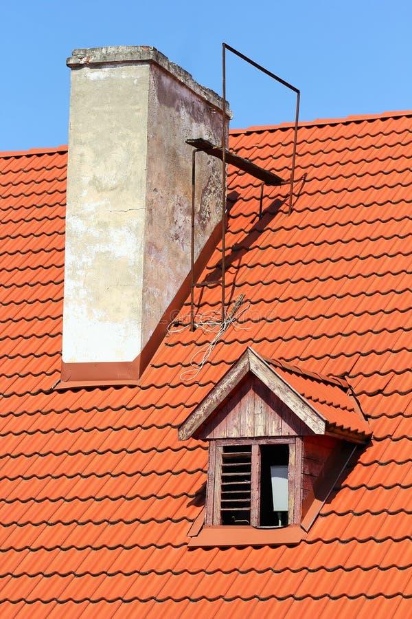 Pieza del tejado de teja roja iluminado por el sol con la chimenea y la ventana viejas del vintage fotografía de archivo