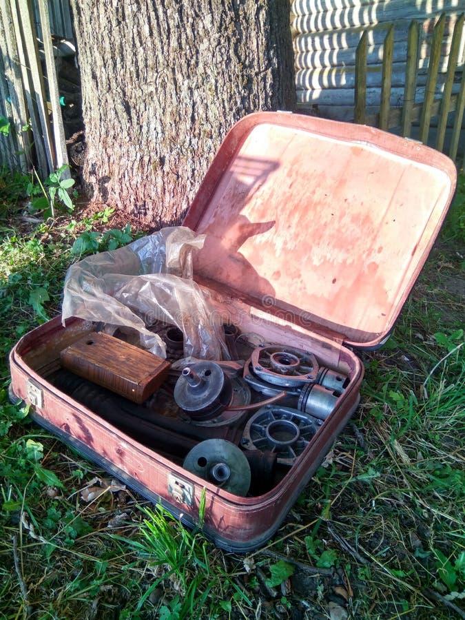 Piezas de acero para la reparación de la máquina en una maleta vieja imagenes de archivo