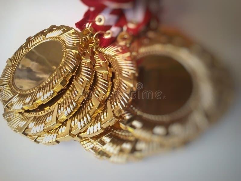 Piezas de medalla de oro con bordes rayados foto de archivo