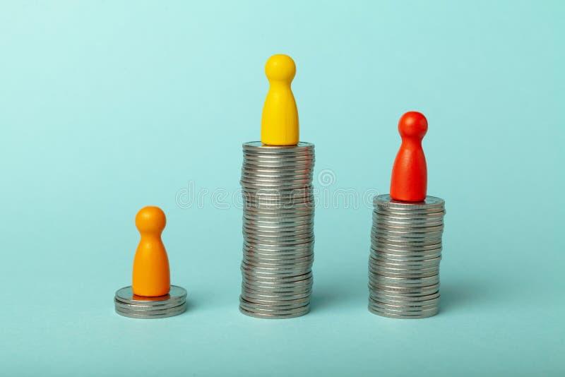 Piezas sobre pilas de monedas, Concepto de diferentes niveles de ingresos y beneficios financieros imagen de archivo libre de regalías