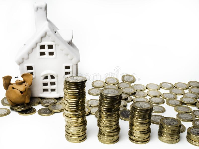 Pig bank, coins and house on white table. save and investment for buy house concept .for the future. save money concept. Isolated on white royalty free stock images