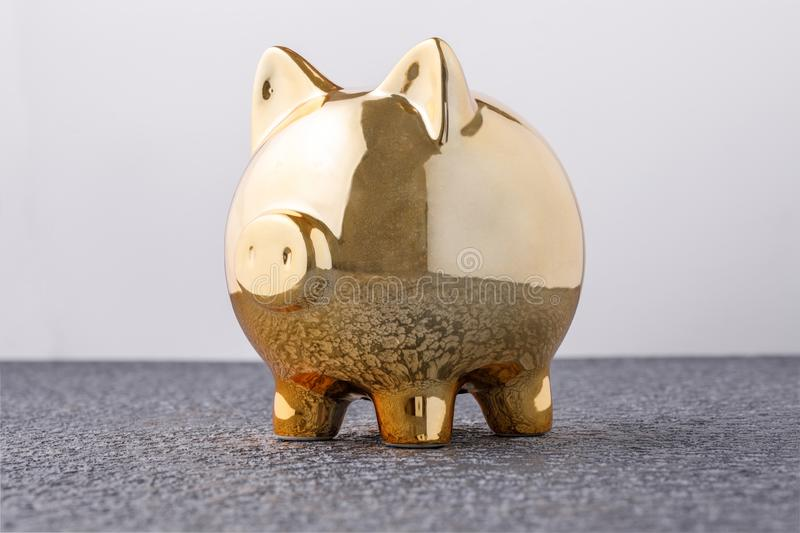 Pig money box golden on black background concept of financial insurance, protection, safe investment or banking. Close-up stock photos