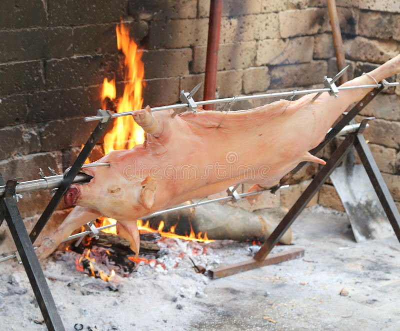 pig on the spit and slowly cooked on the large fireplace stock images