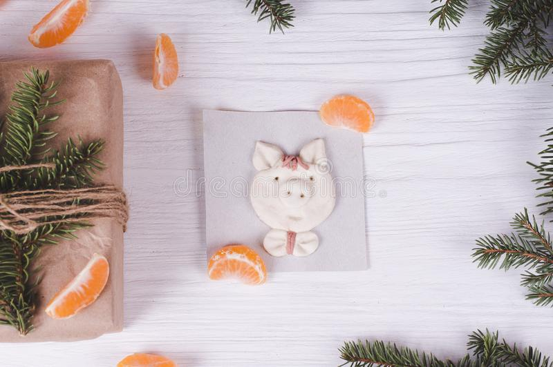 Pig - the symbol of the year, molded by child, tangerine slices and fir branches with Christmas gift box. kid`s art concept. stock photo