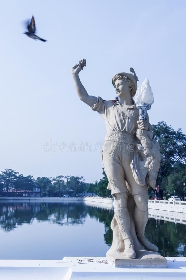 Pigeon perching and flying are on the statue near the lake at Bang Pa-In Palace royalty free stock photography