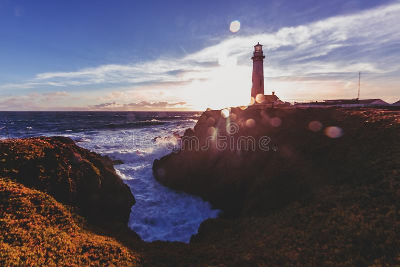 Pigeon Point Lighthouse on Northern California Pacific Ocean coastline just before sunset with an artistic sun flare, vintage look. Artistic sun flare with a royalty free stock images