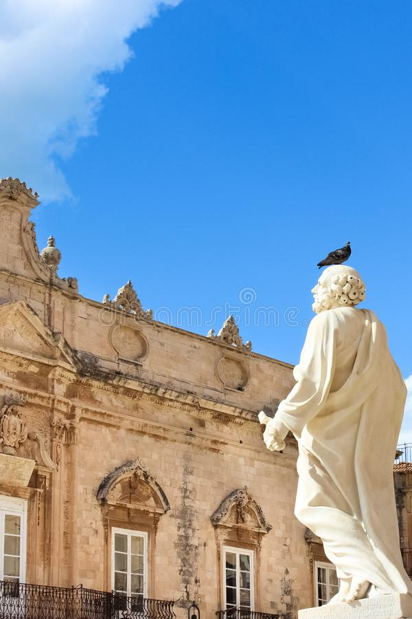 Pigeon sitting on marble statue belonging to Cathedral of Syracuse on Piazza Duomo in Syracuse, Sicily, Italy. Pigeon droppings. Are big problem while stock photo