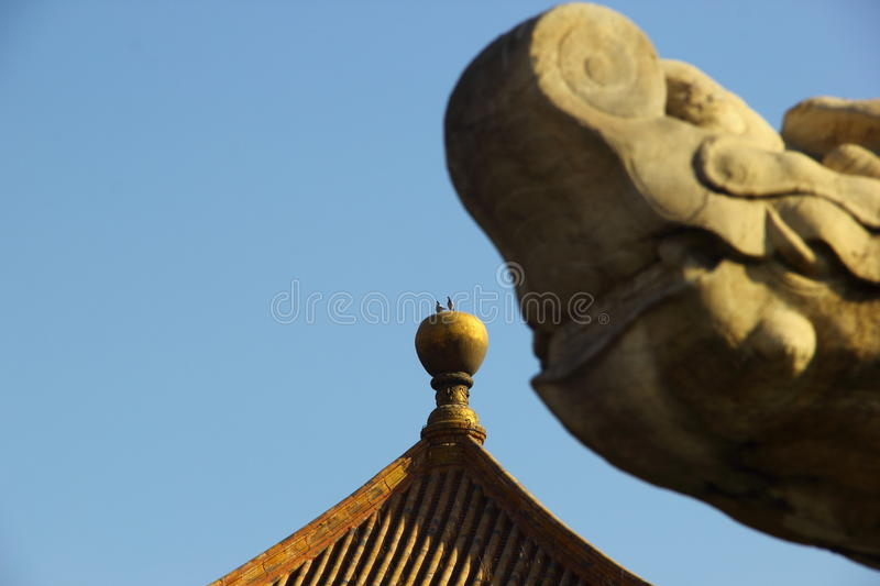 Pigeons staying on golden spire. Two pigeons stay on the golden spire of a pagoda in the Forbidden city stock photo