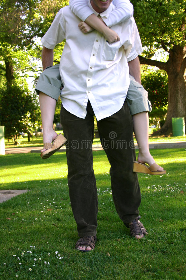 Piggy-back ride. Young couple playing around in the park stock photo