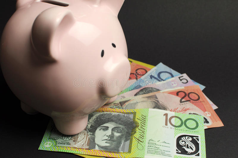 Piggy Bank with Australian money against a black background. Pink Piggy Bank with Australian money against a black background, for savings concept stock photography
