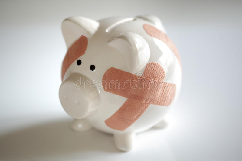 Piggy bank with band aids royalty free stock photography