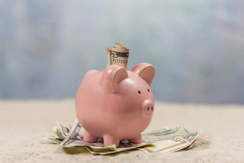 Piggy Bank On Beach With Money Shallow DOF. Horizontal shot of a pink piggy bank from the side sitting on a pile of money with money in its slot on a sand beach stock photos