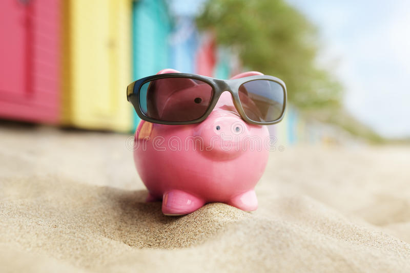 Piggy bank on beach vacation stock photos