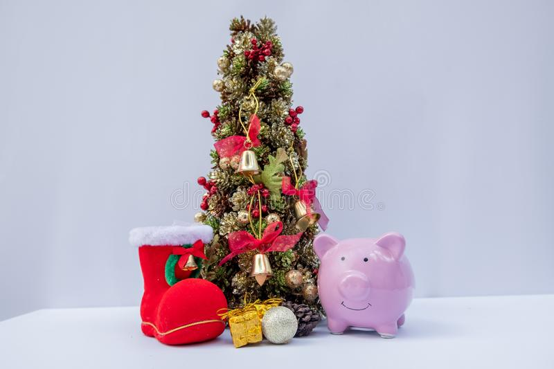 Piggy bank and Beautifully decorated Christmas tree with a holiday party beginning in the new year and crossing to year 2020 stock image