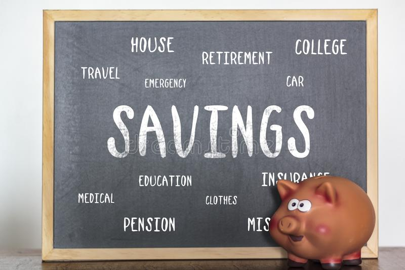 Piggy bank and blackboard with the word savings. Saving money and life expenses concept.  royalty free stock photos