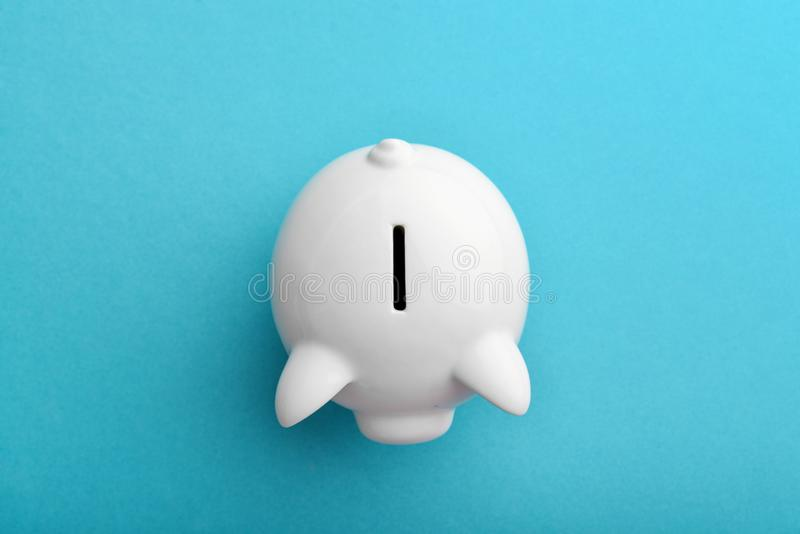 Piggy bank on blue. Background, top view stock photo