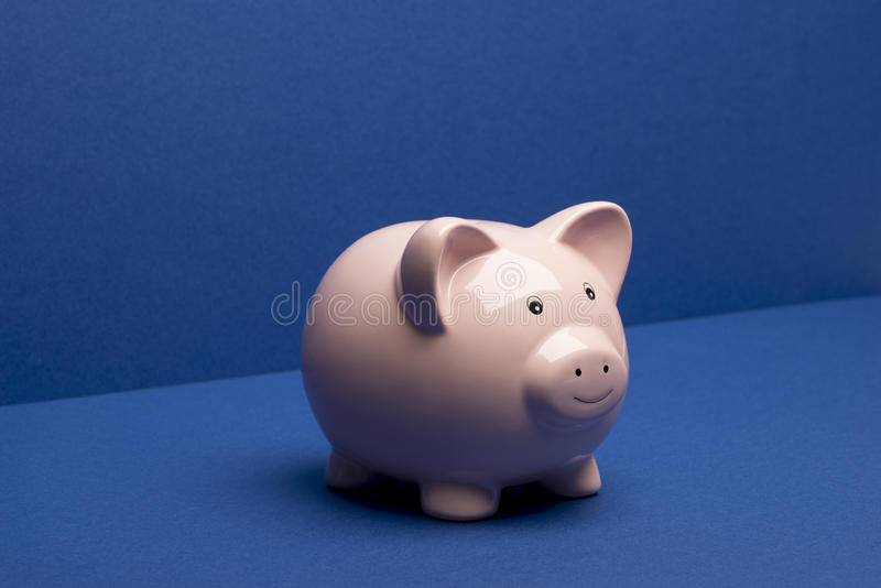 Piggy Bank on Blue Floor and Wall Background. Piggy bank on a blue floor and wall background stock photos
