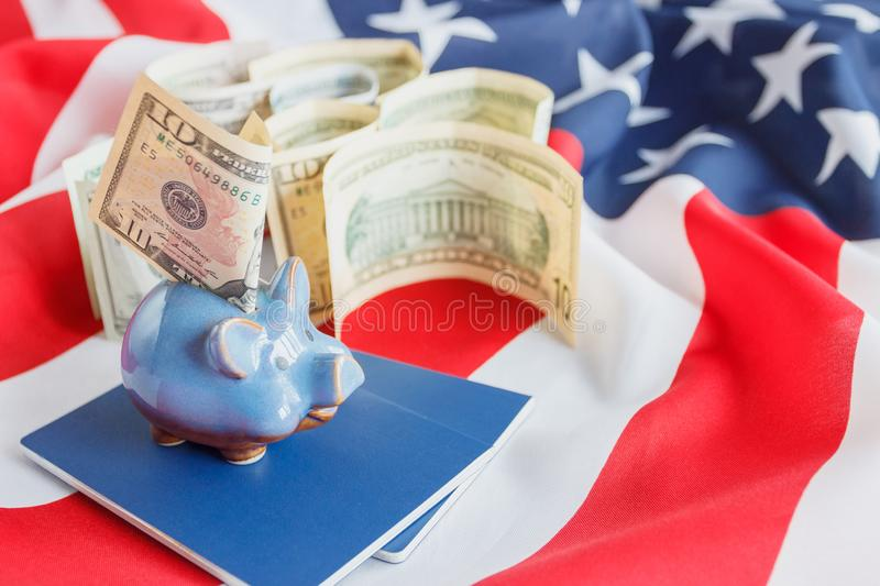 Piggy bank, blue passports and American dollars on the national flag of United States of America. Background, top view stock photo