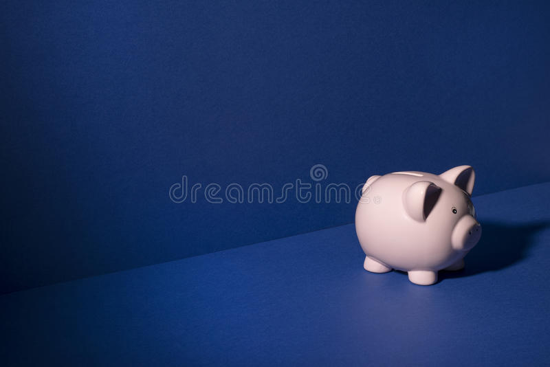 Piggy Bank On Blue Wall and Floor Background Copy Space. Piggy bank on blue wall and floor background with copy space stock image