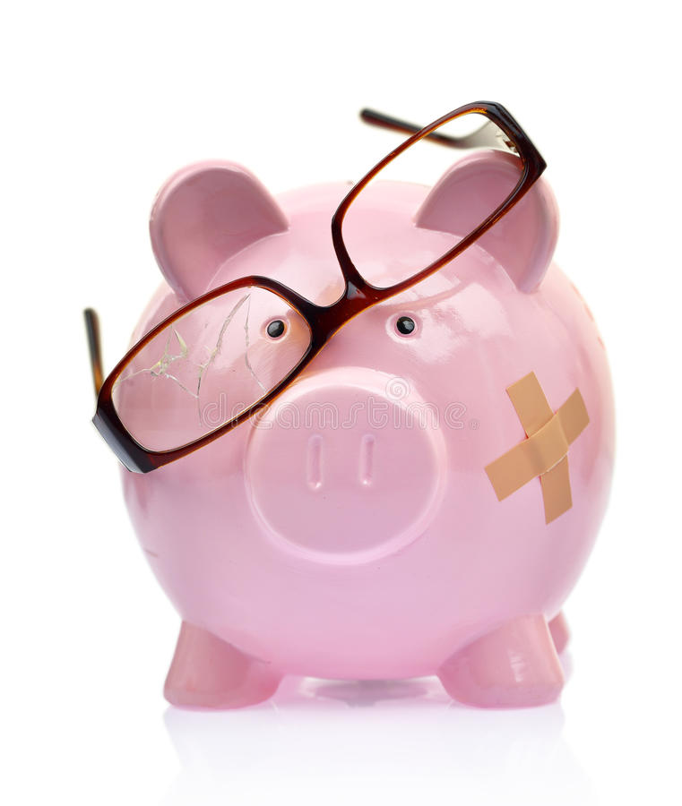 Piggy bank with broken eyeglasses royalty free stock image