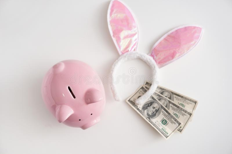 Piggy bank, bunny ears and dollars on white background. Concept of saving money for holiday royalty free stock image