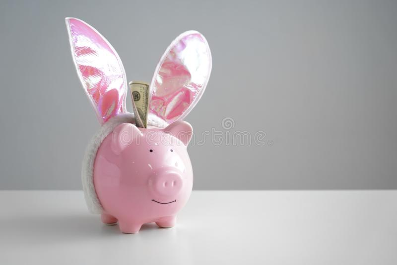 Piggy bank with bunny ears on table. Concept of saving money for holiday stock photography