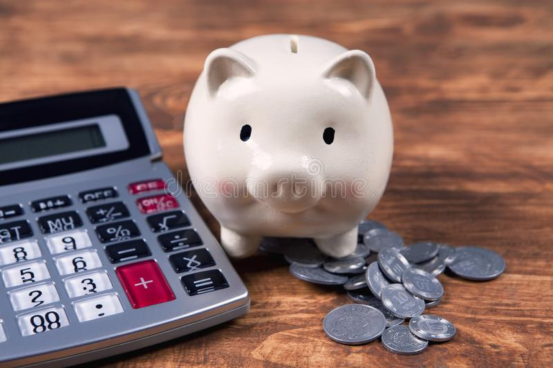 Piggy bank, calculator and coins.  stock photo