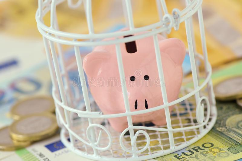 Piggy bank closed in a cage on euro money - Concept of savings blocked royalty free stock image