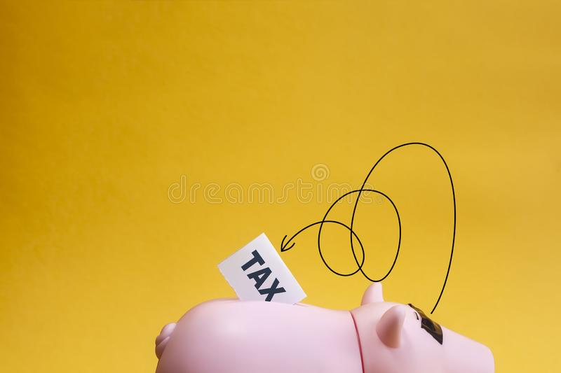 Hiding from tax concept. Piggy bank closed eyes with tape and don`t want see tax stock photos