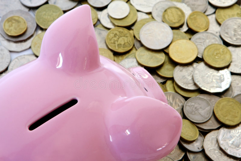 Piggy Bank with Coins. Pink piggy bank looking over a pile of coins. Vertical perspective stock photo