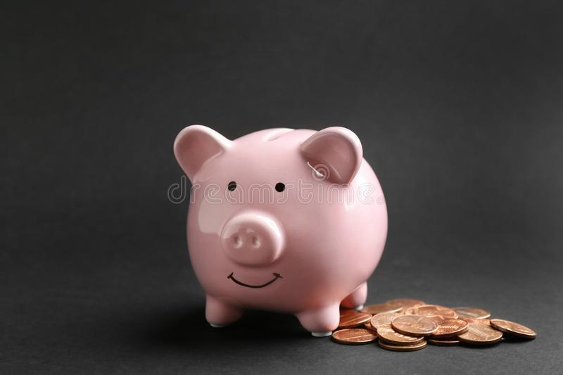 Piggy bank and coins on black. Background stock photography
