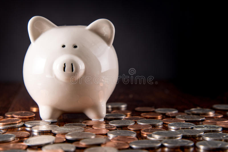Piggy Bank & Coins. Piggy Bank on dark Hardwood Floor surrounded by scattered coins / USD money with a black background