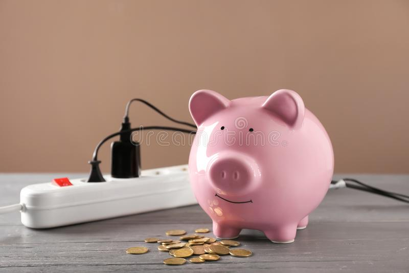 Piggy bank, coins and power strip on table. Electricity saving concept stock photography