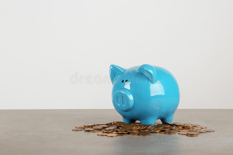 Piggy bank and coins on table against white background. Space for text stock photography