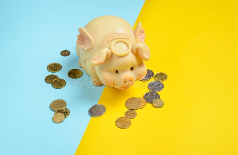 Piggy bank with coins on a yellow blue background. Ukrainian economy, Ukrainian flag. royalty free stock images
